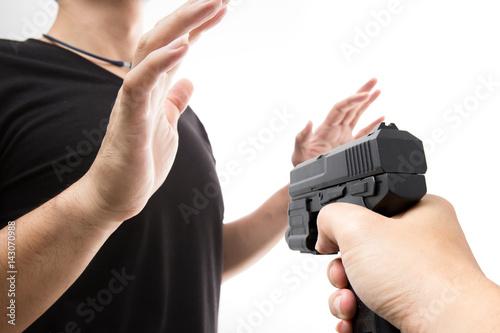 Robber with a gun robbing intimidate a man surrender Fototapeta