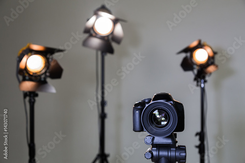 Foto op Canvas Licht, schaduw Digital SLR camera and three spotlights with Fresnel lenses. Manual interchangeable lens for filming. Shooting in the interior with artificial light. Equipment for movies.