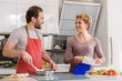 Cheerful man and woman preparing breakfast at home