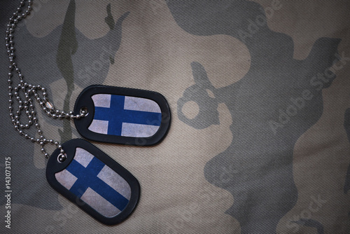 Fotografia  army blank, dog tag with flag of finland on the khaki texture background