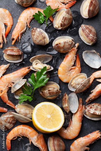 Aluminium Prints Seafoods Fresh seafood on stone table. Scallops and shrimps