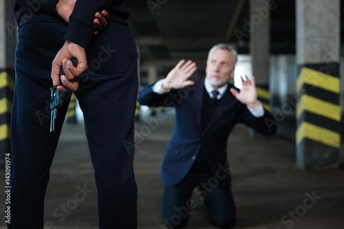 Fotografía  Selective focus of a handgun being held behind the back