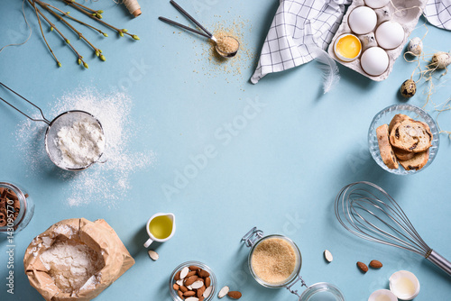 Obraz Baking or cooking background frame. Ingredients, kitchen items for baking cakes. Kitchen utensils, flour, eggs, almond, cinnamon, oil. Text space, top view. - fototapety do salonu