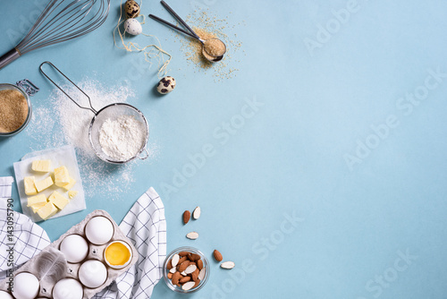 Tuinposter Bakkerij Healthy baking ingredients - flour, almond nuts, butter, eggs, biscuits over a blue table background. Bakery background frame. Top view, copy space.