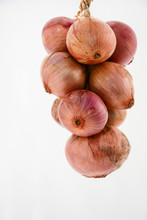 Hanging Bundle Of Brown Onions On White Background