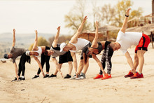 Group Friends Exercising On Th...