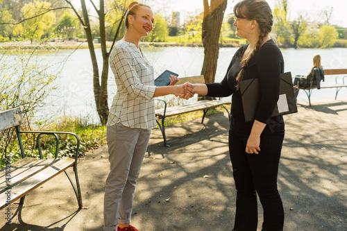 Fototapeta Two female shaking hands in park obraz na płótnie