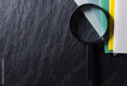 Foto  Lupe und buntes Notizbuch auf schwarzem Hintergrund