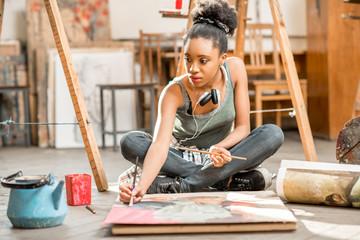 Prekrasna studentica afričke nacionalnosti slika na podu u sveučilišnoj učionici