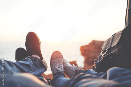 Fototapeta Couple lying at sunset near the ocean in the van's trunk, close-up of shoes of woman and man, romantic relationships obraz na płótnie