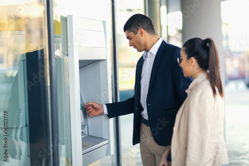 Fotografia, Obraz Young people with credit card standing next to the ATM to withdraw money