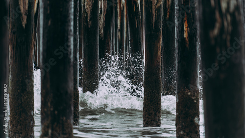 Papiers peints Forets Beach water wave splash poles wood under bridge pier