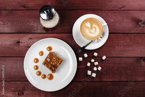Foto op Plexiglas a piece of chocolate brownie and caramel sauce, a cup of cappuccino on a white plate. Top view