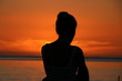 Lady during Sunset / Young Lady enjoys the beautiful sunset at the beach of the Indian Ocean, Mauritius, Africa.