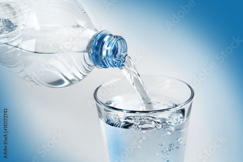 Papiers peints Eau Pouring water from bottle into glass