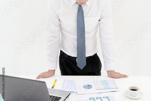 Young businessman standing behind office desk and working