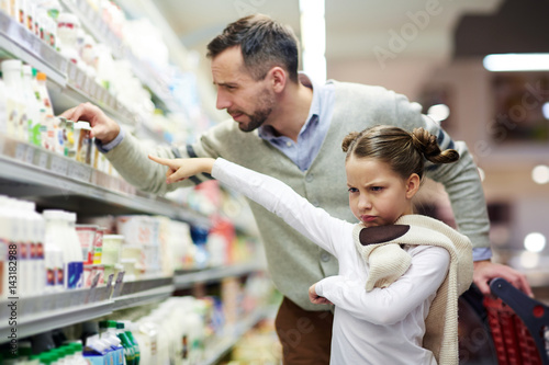 Fotografia, Obraz  Capricious daughter asking her father to buy her tasty yoghurt in supermarket
