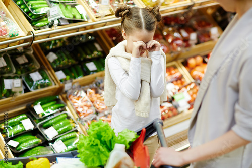 Valokuva  Girl crying on background of supermarket-shelf in front of her mother