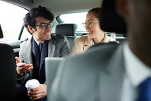 Portrait Of Two Successful Business People Riding On Backseat Of Taxi: Smiling Cheerfully And Talking On The Way To Work