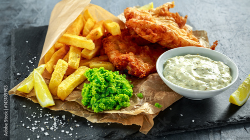 Fotografía  British Traditional Fish and chips with mashed peas, tartar sauce on crumpled paper