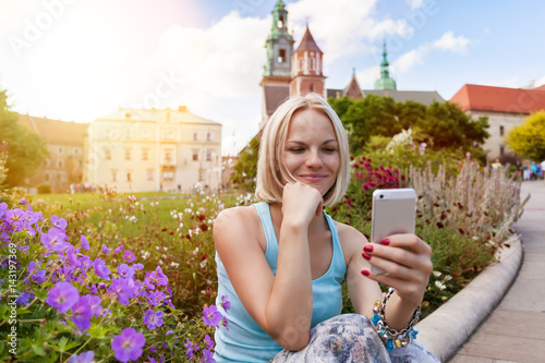 Female traveler in a blue T-shirt and a long skirt sitting and looking in a mobile phone on the background of Wawel Castle. Krakow, Poland