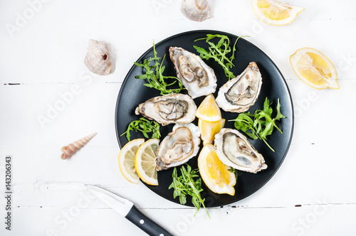 Staande foto Schaaldieren Oysters with lemon fruit on a black plate on a white wood table