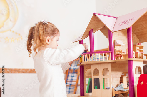 Photo  Girl playing with a dollhouse