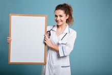 Happy Female Doctor Showing Blank Board