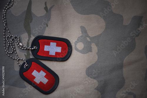 Fotografia  army blank, dog tag with flag of switzerland on the khaki texture background