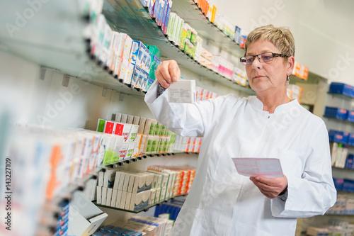 In de dag Apotheek Apothekerin sucht Medikamente aus einem Regal