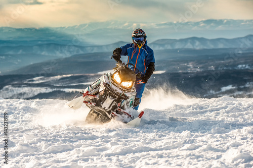 Poster Glisse hiver Rider on the snowmobile in the mountains. active drive