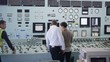 Workers in power plant control room looking at control panel & checking system