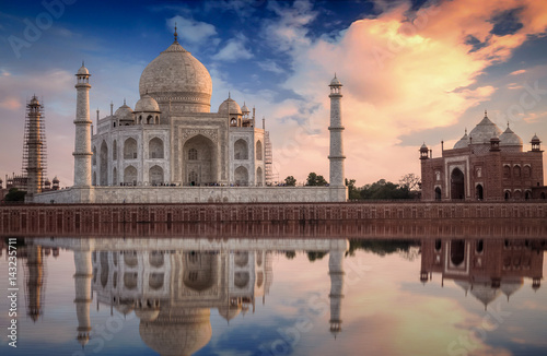 Poster Artistique Taj Mahal with a scenic sunset view on the banks of river Yamuna. Taj Mahal is a white marble mausoleum designated as a UNESCO World heritage site at Agra, India.
