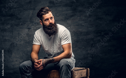Tableau sur Toile Bearded male with tattoo on arm dressed in a white t shirt sits on a wooden box