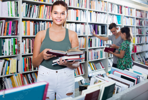 portrait of  teenage girl customer looking at open book standing among bookshelv Canvas
