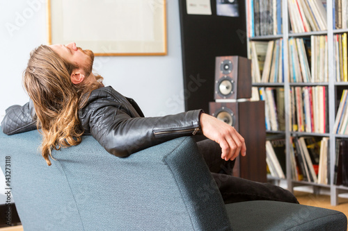 Audiophile leaning back on a couch listening to music Canvas Print