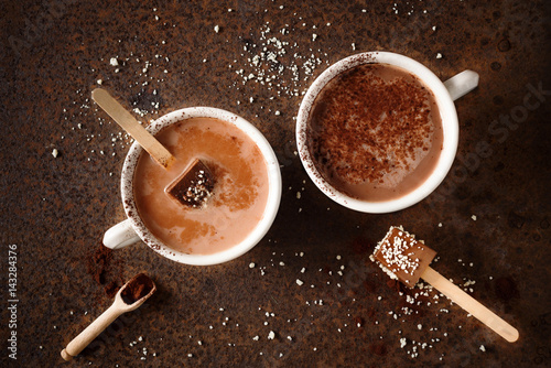 Two cups of hot chocolate with cocoa powder Chocolate on stick Top view