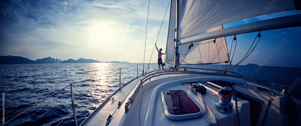 Fototapety, obrazy: Young man standing on the yacht in the sea at sunset