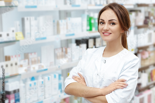 Tuinposter Apotheek Caring customers with a smile. Horizontal portrait of a beautiful pharmacist smiling to the camera cheerfully posing in the drugstore.