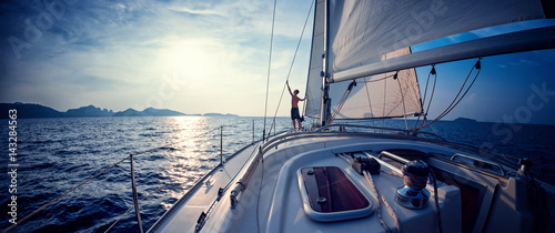 Young man standing on the yacht in the sea at sunset Fototapeta