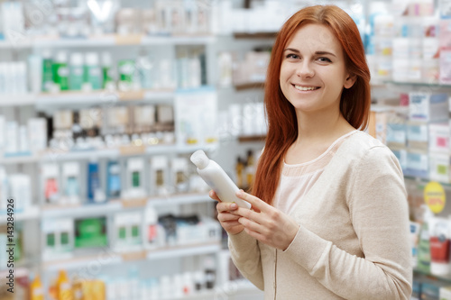 Foto op Canvas Apotheek Happy to decide. Portrait of a happy pharmacy client holding a medication product looking to the camera smiling.