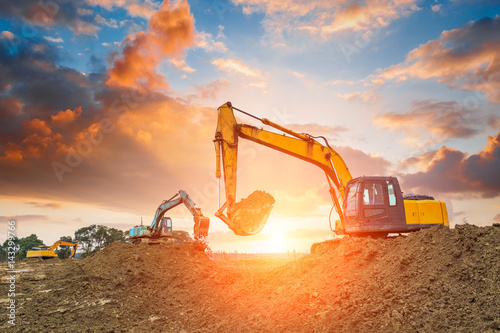 Photo excavator in construction site on sunset sky background