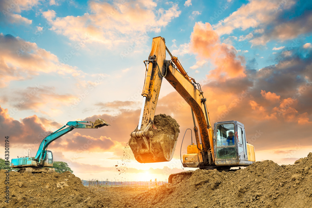 Fototapeta excavator in construction site on sunset sky background