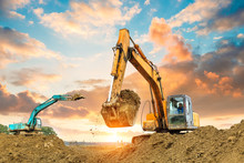 Excavator In Construction Site On Sunset Sky Background