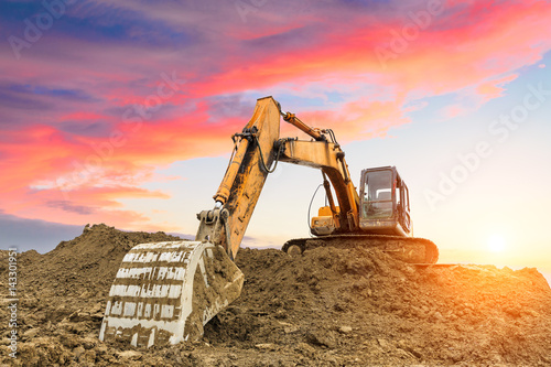 excavator in construction site on sunset sky background Fototapet
