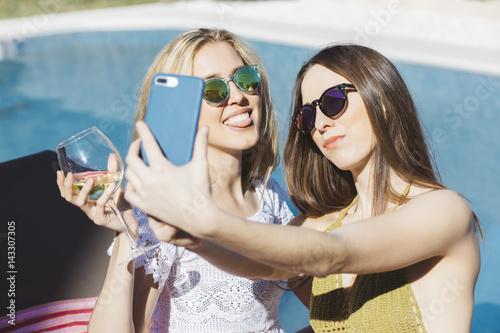 Plakat Młode kobiety pozuje dla selfie w pływackim basenie
