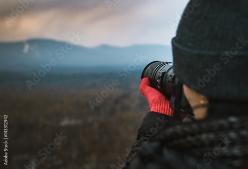 Spoed Foto op Canvas Grijze traf. Girl photographer takes pictures of a magnificent mountain landscape