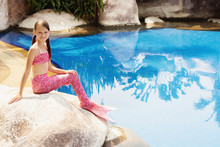 Mermaid Girl With Pink Tail On Rock At Poolside