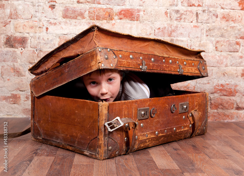 Fotomural  A boy looks out from an old leather suitcase