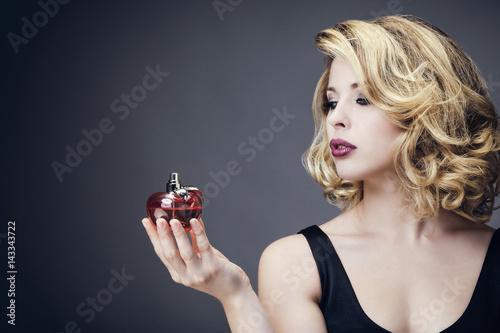 Fotografía Jeune femme en tenue de soirée, de profil, un parfum dans la main